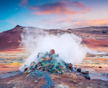 Steaming fumarole in geothermal valley Hverarond. Exotic summer sunrise of volcanic Icelandic landmark, Reykjahlid village location, north Iceland, Europe. Artistic style post processed photo.