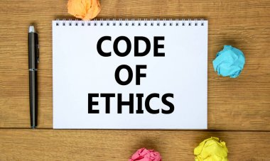 Code of ethics symbol. Words 'Code of ethics' on beautiful wooden table, colored paper, black metallic pen. Business, code of ethics concept, copy space.