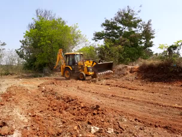 Bangalore, Karnataka, India-Mar 21 2021: Closeup of JCB cleaning land for construction of building at forest or countryside
