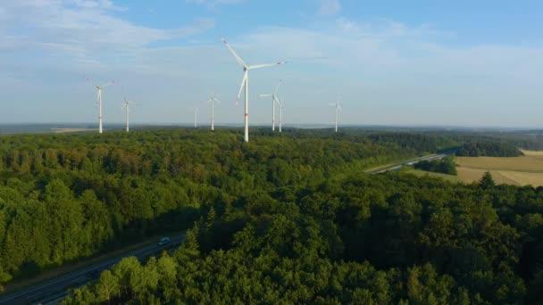 Windräder in Deutschland an einem sonnigen Sommertag in Bayern neben einer Autobahn.