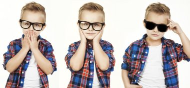 Funny child.fashionable little boy in glasses, jeans, white t-shirt and plaid shirt.stylish kid  in shock and surprise. concept of a fashion children which showed monkey motions: hear nothing, say nothing, see nothing