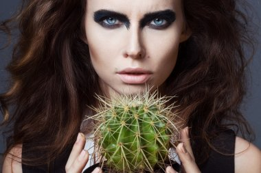 Sexy Beauty Girl with natural Lips and arty black make up on her eyes. Provocative Make up. Luxury Woman with Blue Eyes. Fashion Brunette Portrait on grey background holding a green cactus. Gorgeous Woman Face. Long Hair
