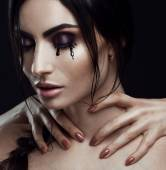 A photo of beautiful girl with perfect art makeup , painted black tears on her cheek and holding her hand on her  neck. Mystical and mysterious portrait