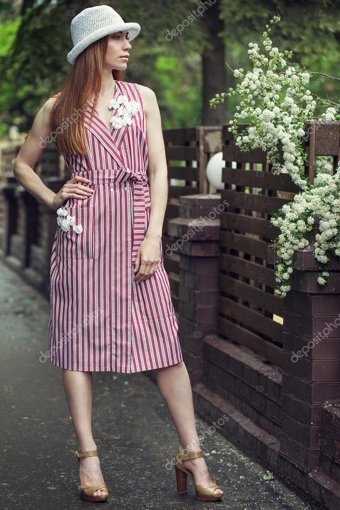 d917a134fbe Όμορφο κομψό νεαρό κορίτσι ντυμένο με ρούχα casual (φόρεμα και πάνινα  παπούτσια) βόλτες στους δρόμους της πόλης, μετά τη βροχή. η έννοια της  μόδας ρούχα για ...