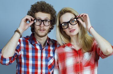 Portrait of gorgeous blond fashion man and woman (couple) in casual shirt  wearing trendy eyeglasses posing over blue background. Perfect skin and hairdo. Vogue style. Close up.  Eyewear concept.
