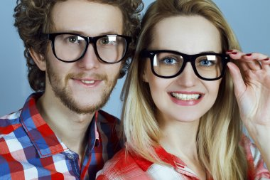 Portrait of gorgeous blond fashion man and woman (couple) in casual shirt  wearing trendy eyeglasses posing over blue background. Perfect skin and hairdo. Close up. Studio shot. Eyewear concept.