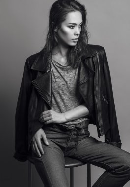 Portrait of a fashionable model with natural make up and perfect skin, dressed in men's jeans, grey shirt, black jacket and sneakers.  Studio shot. High fashion look. Monochrome (black and white)  photo