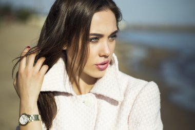High fashion concept. Emotive portrait of beautiful brunette with long  hair and perfect make up, wearing in pink coat. the sunny weather on  beach. Italian luxurious style. Outdoor shot