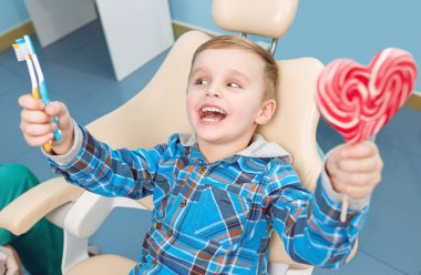 very happy boy after the doctor at the clinic, holding a heart candy and toothbrushes, and beautiful smiles