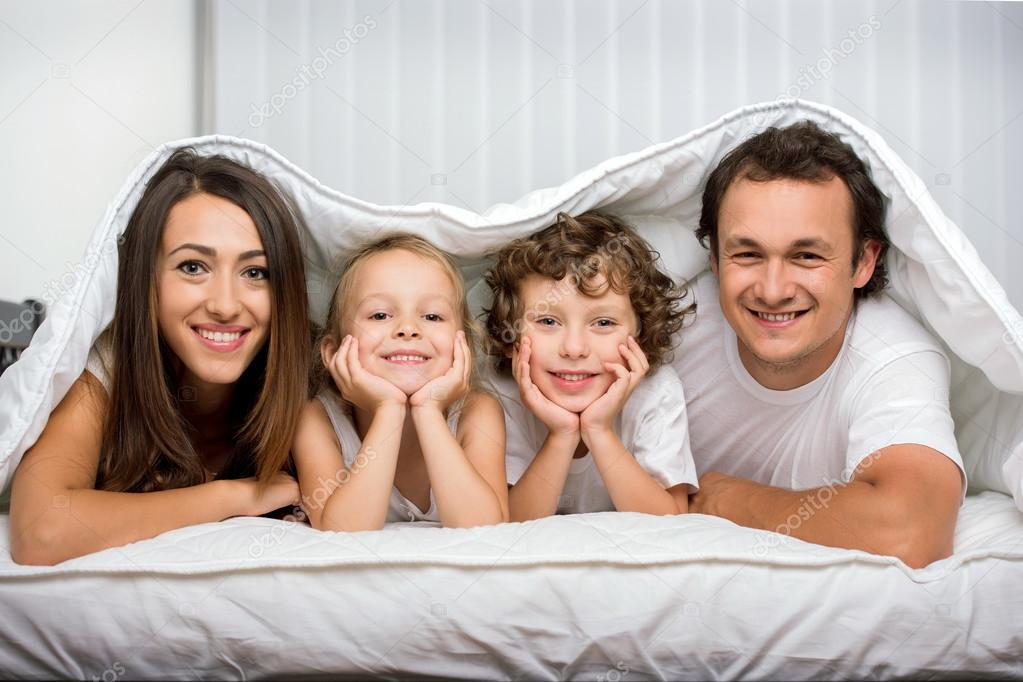 Families with children in bed under a blanket stock vector