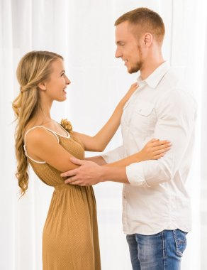 Beautiful couple dancing at home and looking to each other against window. stock vector
