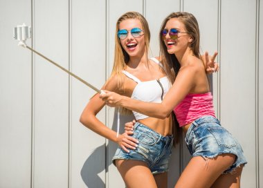Two attractive girlfriends are making selfie photo with selfie stick, standing against the wall outdoor. stock vector