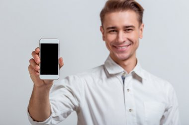 Portrait of attractive young blond businessman in white classical shirt smiling and holding smartphone, standing against gray background stock vector