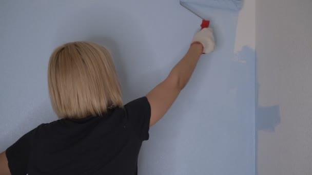 Eine schwangere Frau steht vor einer weißen Wand und streicht über ihren Bauch.Konzept von Körperhaltung und Schwangerschaft