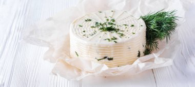 Pickled cheese with dill, spices and garlic on a white wooden background. Selective focus