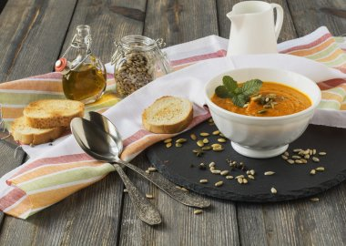 Simple soup of carrots with ginger on an old wooden table background.Selective focus.