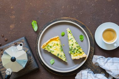 Sliced quiche pie with spinach, green peas, asparagus beans and egg topping on a ceramic plate on a brown concrete background. French cuisine. Savory pastry recipes