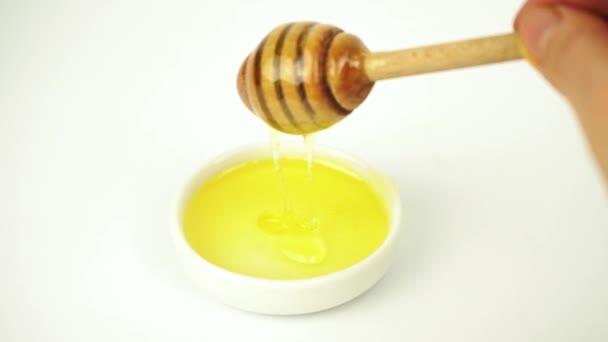 Tekutý med s dřevěnou tyčinkou z malého bílého talíře