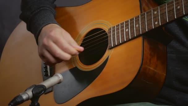 Hraje na akustickou kytaru. Zblízka vystřelit na tělo kytary. Hudební video pozadí, koncept