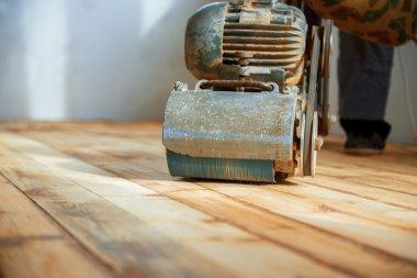 Worker polishing parquet floor with grinding machine