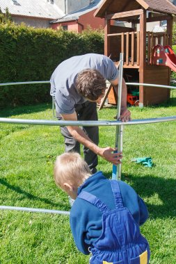 Father and son when installing large garden trampolines.