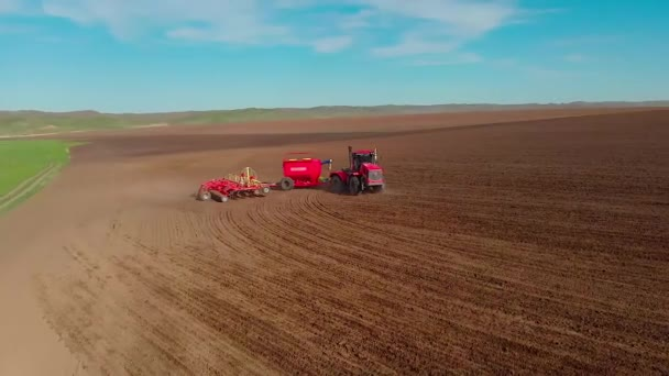 Agricultural modern tractor plough plows ground before planting the crop, preparing soil for sowing, view from the drone
