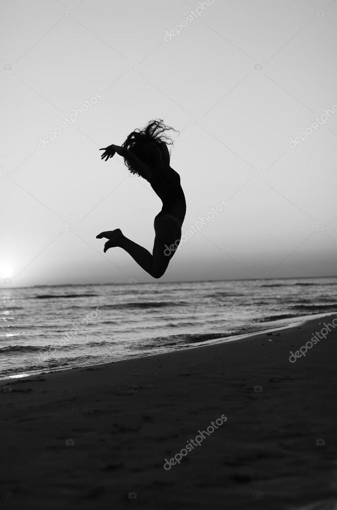 girl doing gymnastics on the beach at sunset