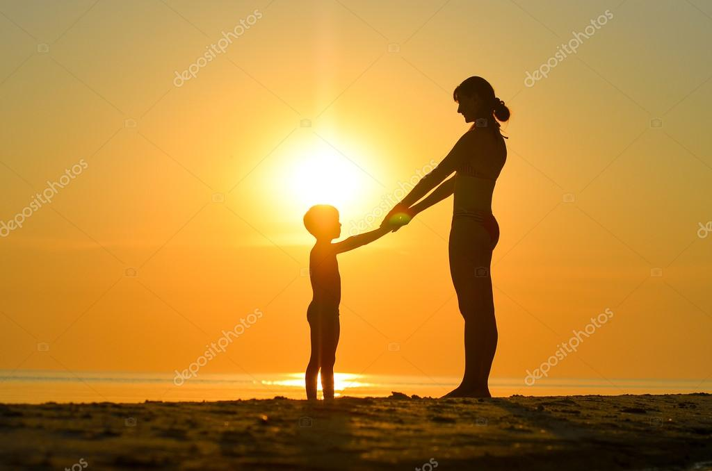 Mother with child sit on the beach at sunset