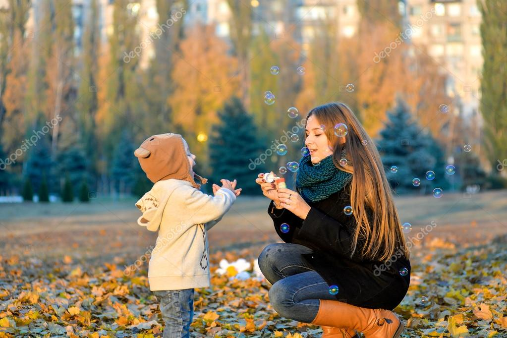 Little Boy Playing With His Sister In The Park In Autumn Girl Blowing Soap Bubbles And Little Brother Catches Them Cheerful Happy Kids Playing In The