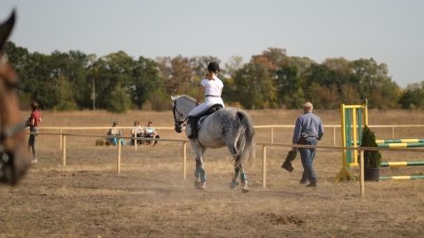 Eine Reiterin trainiert vor einem Springwettbewerb. Pferdesport, Springwettbewerb.