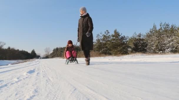 Frohe Winterferien. Winterspaziergang von Mutter und Tochter im Wald. Mutter schlittert ihre Tochter im Schnee im Park. Winter-Familienurlaub im Park.