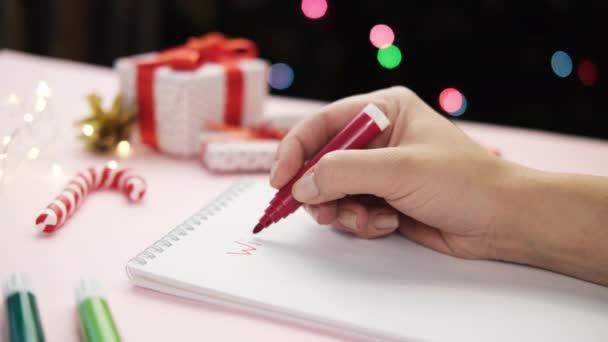 Ženská ruka píše seznam přání na list papíru plstěným perem. na vánoční pozadí bokeh. Koncept nového roku, plány a přání.