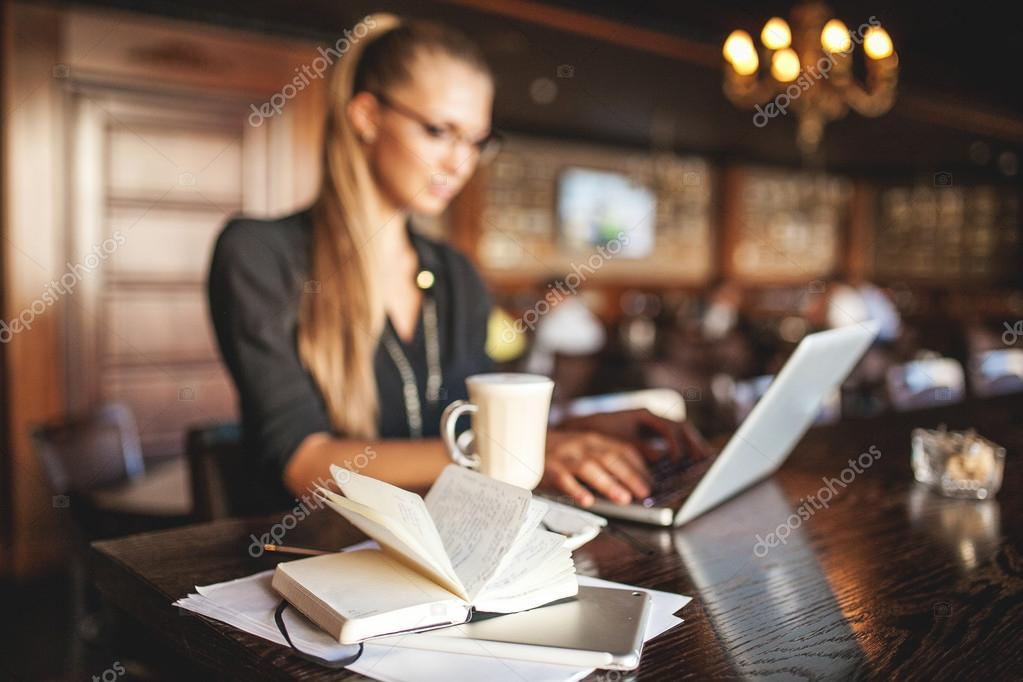 Woman in glasses with coffee and laptop