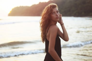 Young beautiful woman with long curly hair at the seaside under the evening sunset