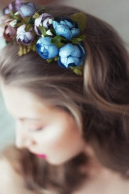 Portrait of beautiful woman with flowers in hair and blue eyes