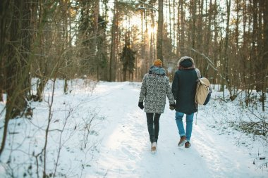Young hipster couple having a walk in winter forest