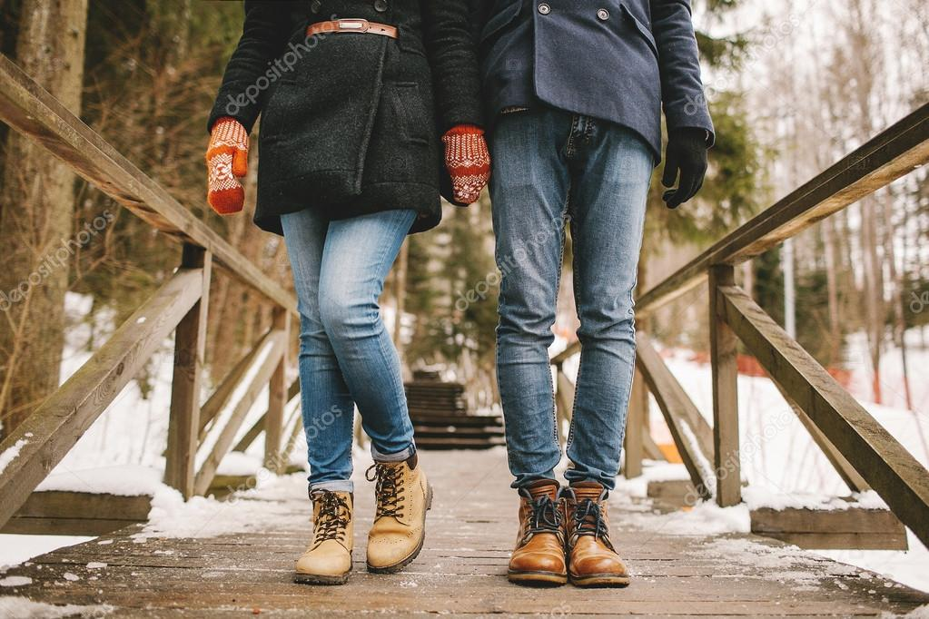 Couple holding hands standing in a winter forest straight