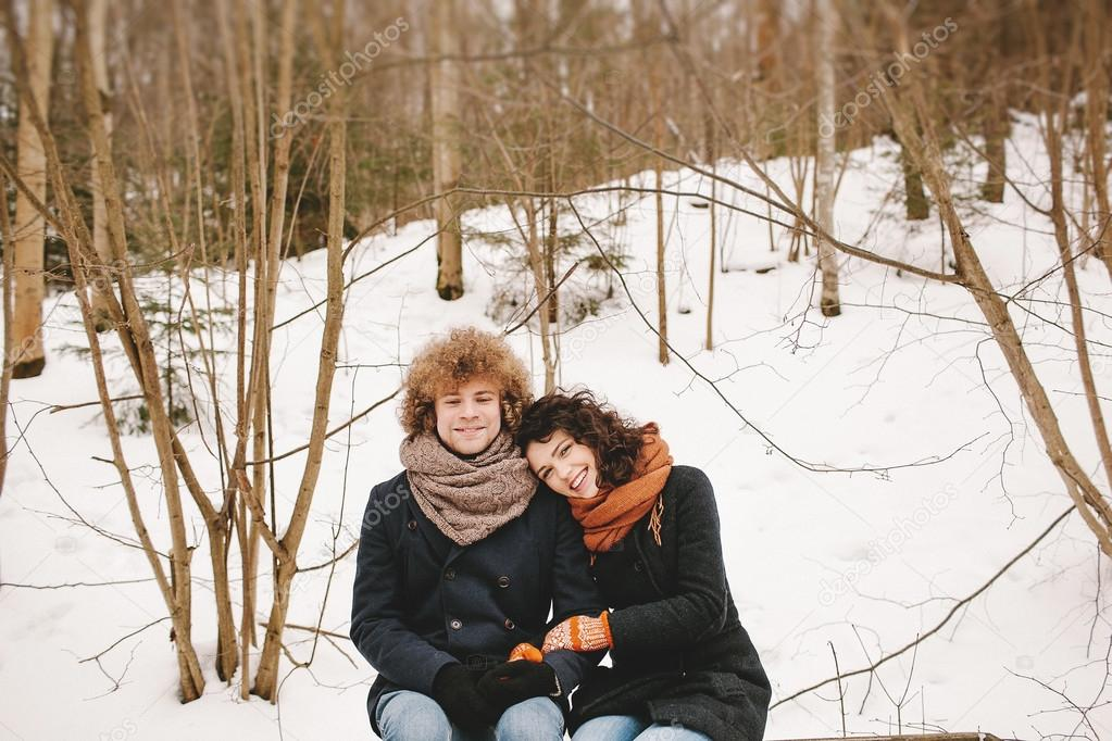Young couple sitting in winter forest together