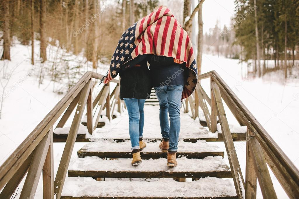 Couple walking winter park under american flag style cloth