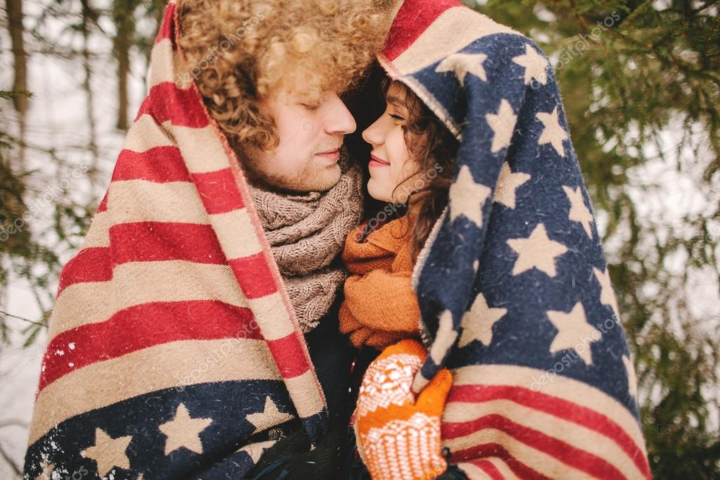 Couple looking at each other under stars and stripes rug outdoor