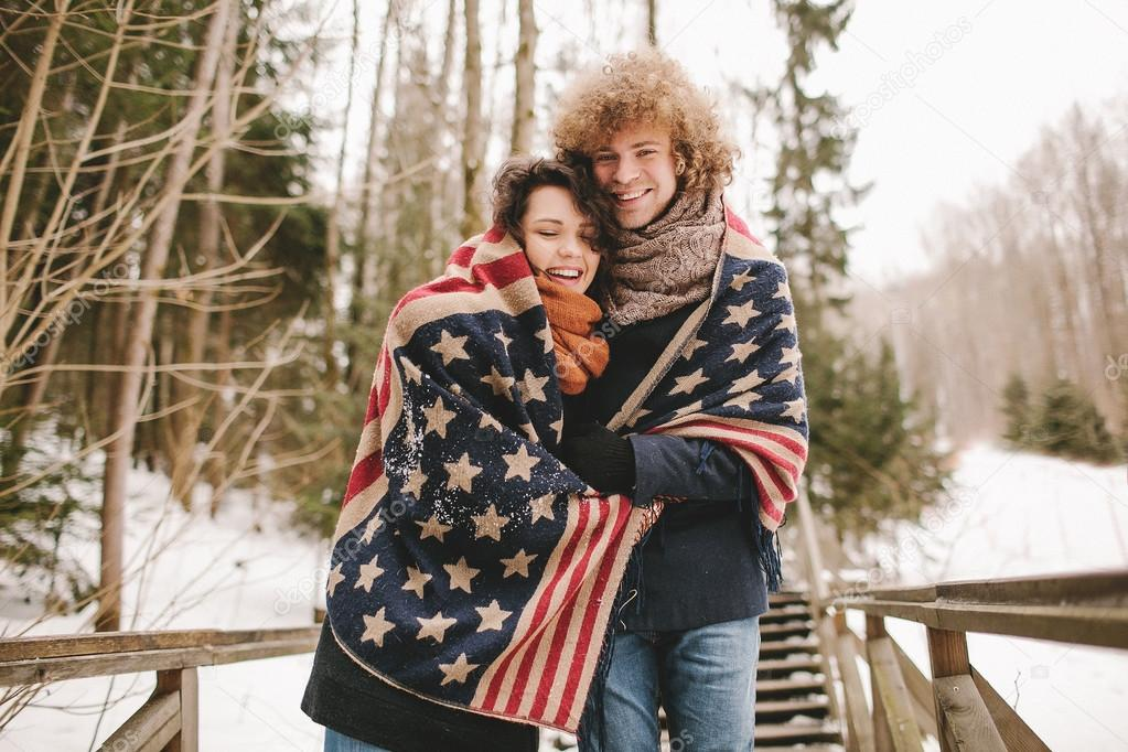 Happy couple under stars and stripes rug in winter park