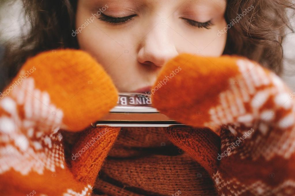 Pretty girl with eyes closed playing harmonica in winter gloves