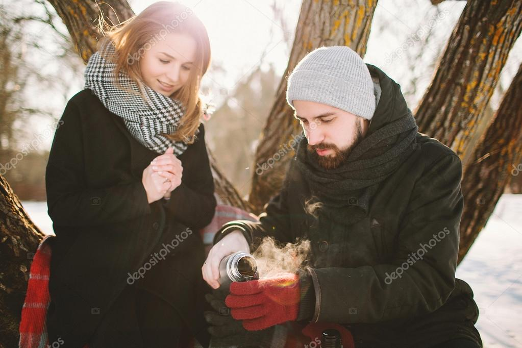 Hipster couple in winter park with hot tea from thermos
