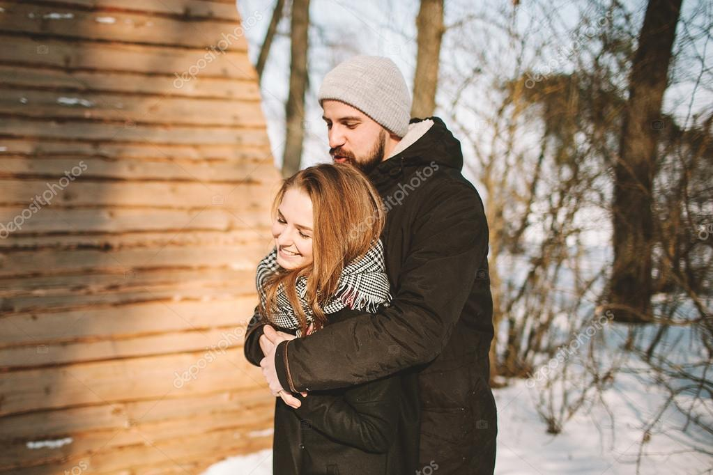 Young hipster couple hugging in winter forest