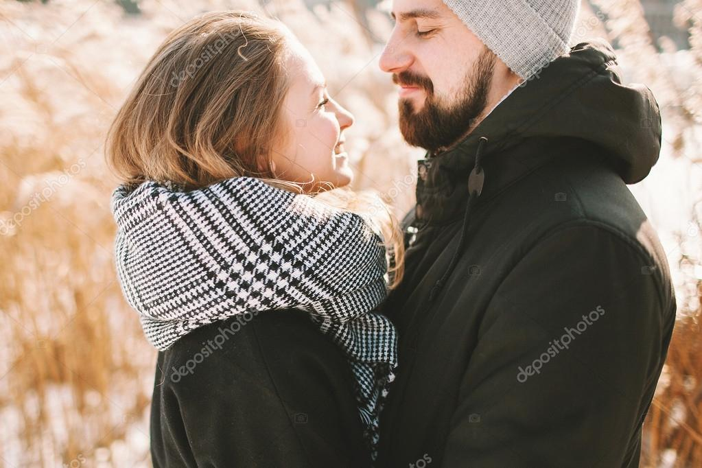 Happy hipster couple hugging near winter lake and reeds