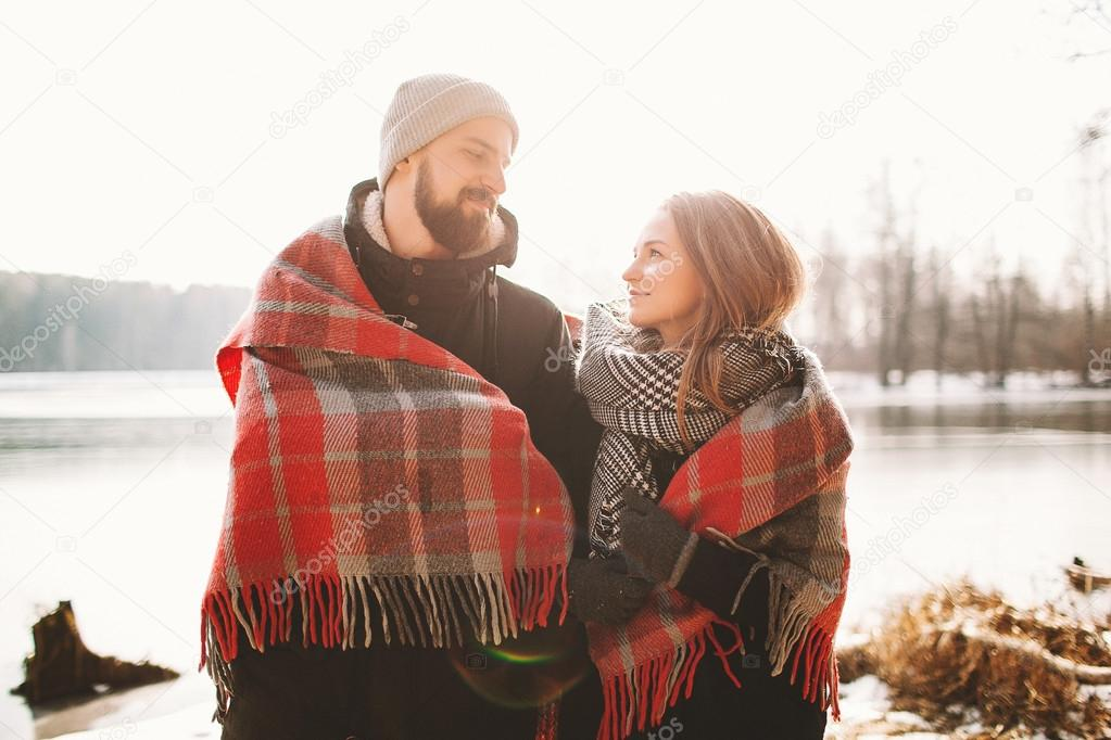 Couple looking each other near winter lake under plaid