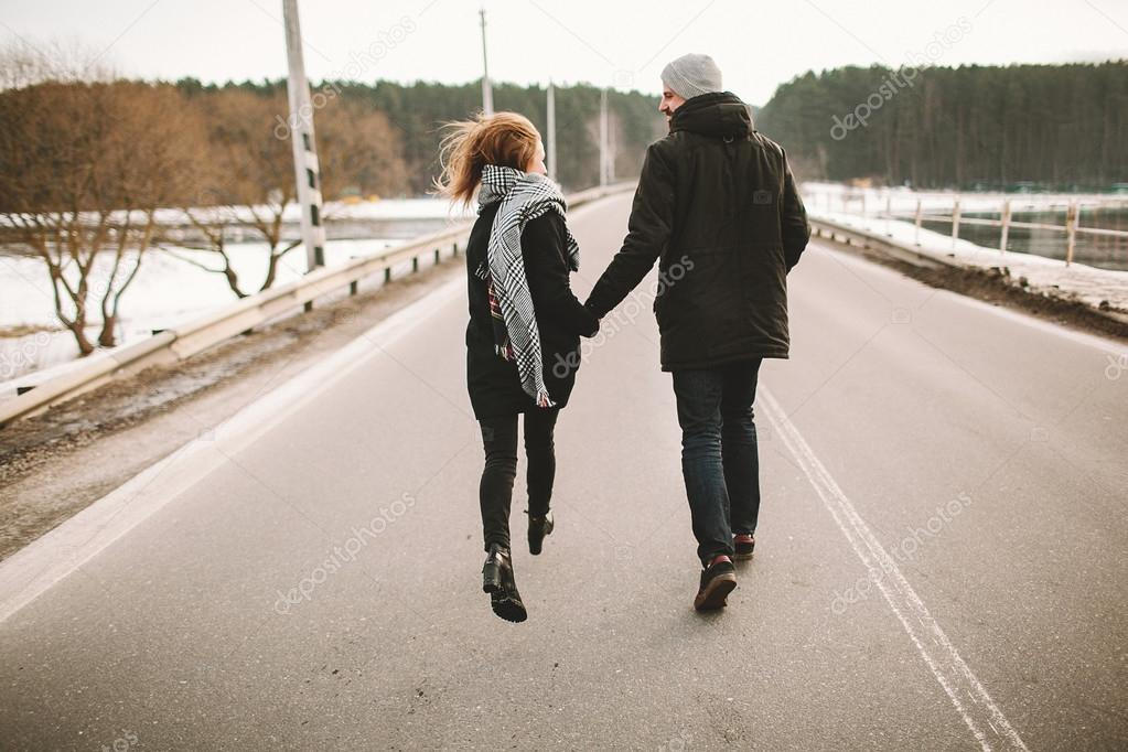 Young couple running on the empty road holding hands