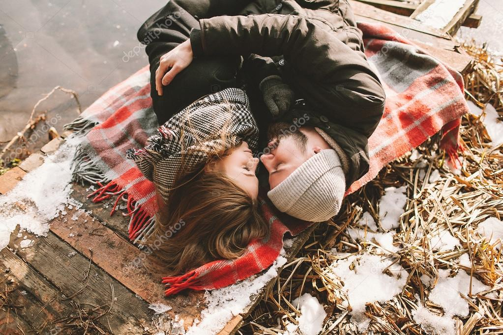 Couple close lying on plaid in winter park