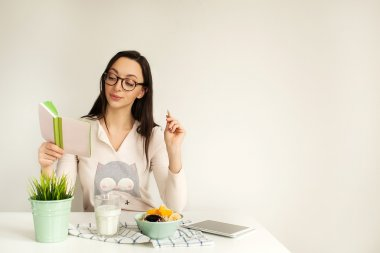 Woman making notes in notepad with healthy food on table