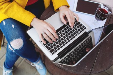 Woman hands typing on laptop tablet and wine in cafe